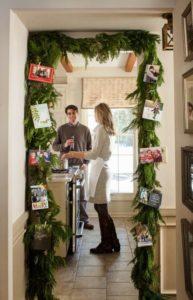 christmas spruce garland around doorway with photos attached