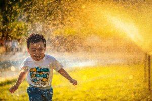 kids playing in sprinkler