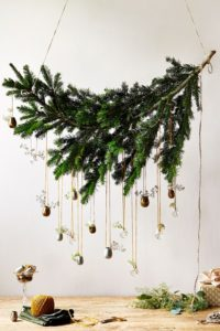 christmas spruce branch hanging above table with planter ornaments